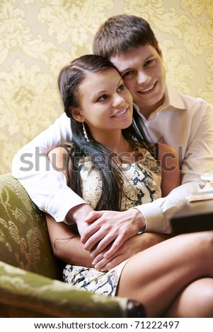 Portrait of boyfriend embracing his girlfriend and sitting on the sofa together - stock photo