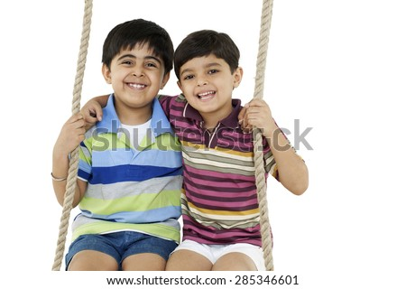 Portrait of boys sitting on a swing - stock photo
