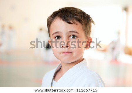 Portrait of brave karate boy training in sport hall - stock photo