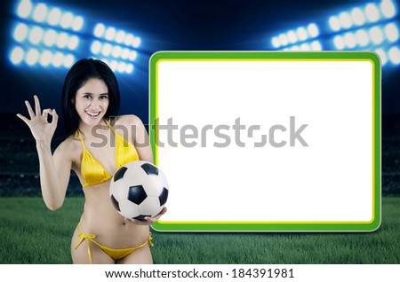 Portrait of Brazil fans giving OK gesture next to copy space. shoot at football stadium - stock photo