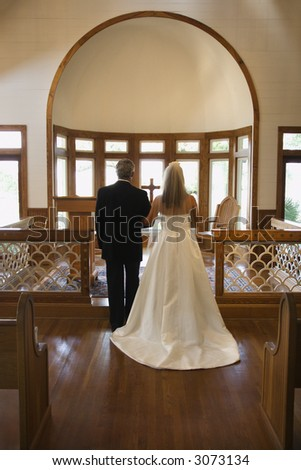 Portrait of bride and groom at alter of a church. - stock photo