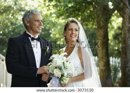 Portrait of bride and groom holding hands outside. - stock photo