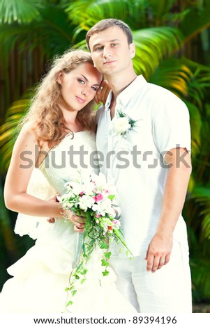Portrait of bride and groom in a tropical garden. - stock photo