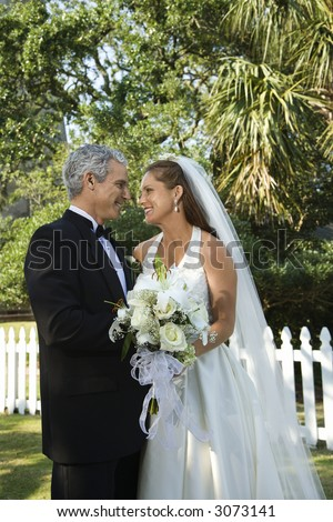 Portrait of bride and groom looking at each other. - stock photo