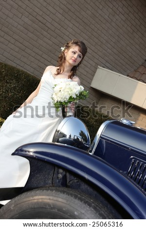 Portrait of bride behind a retro car - stock photo