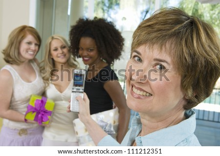 Portrait of bride's mother photographing bride and her friends through mobile phone at  party - stock photo
