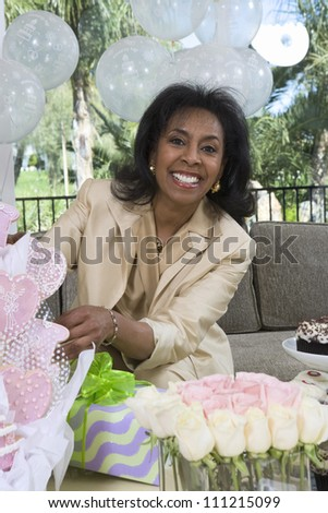 Portrait of bride's mother sitting on sofa with decoration, gift and flowers in the foreground