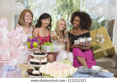 Portrait of bride showing her engagement ring and friends holding gifts at party