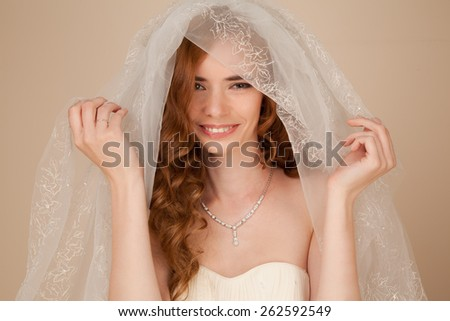 Portrait of bride with curly hairstyle and beautiful makeup smiling - stock photo