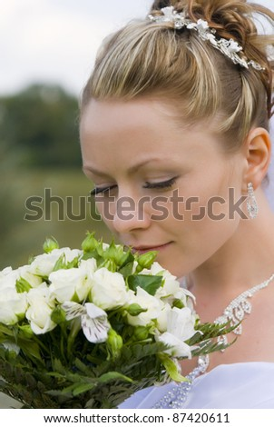 portrait of bride with white bouquet of flowers - stock photo