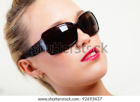 Portrait of brightly lit beautiful young woman in sunglasses