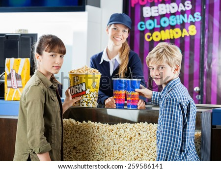 Portrait of brother and sister buying snacks from female seller at cinema concession stand - stock photo