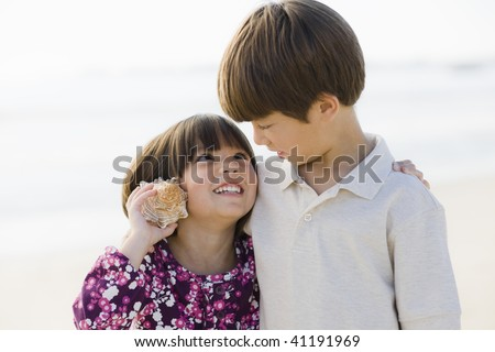 Portrait of Brother and Sister Listening To Shell at Beach