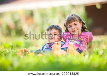 Portrait of  brother and sister smile and laugh together while sitting outdoors. - stock photo