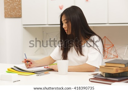 Portrait of brunette Asian student writing something in her exercise-book and drinking delicious cup of tea or coffee in library. - stock photo