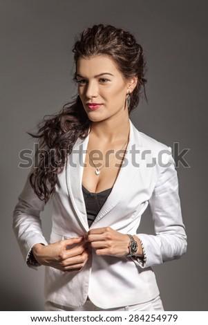 Portrait of brunette beautiful girl posing in white suit. Studio shot - stock photo
