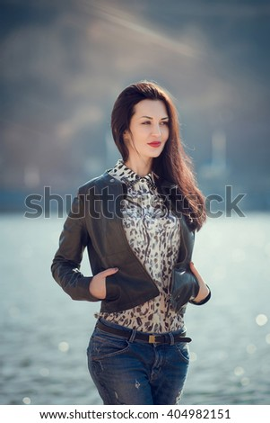 Portrait of  brunette girl in casual clothes walks by the river. Sensual attractive woman  relaxing on the beach and enjoying a warm sunny day. - stock photo