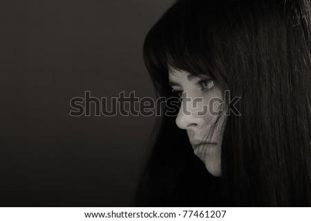 Portrait of brunette girl on dark background - stock photo