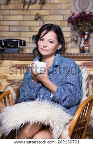 Portrait of brunette in sleepwear with a white cup sitting on the chair - stock photo