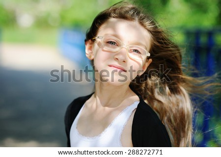 Portrait of brunette kid girl in glasses outdoor in the park - stock photo