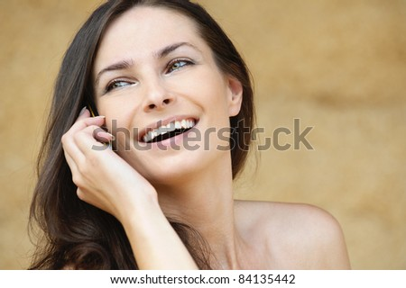 Portrait of brunette laughing young woman speaking on mobile phone against yellow background. - stock photo