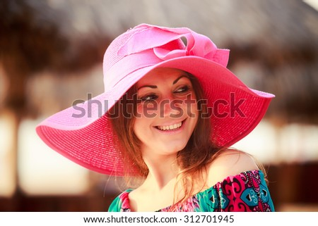 portrait of brunette longhaired girl in big red hat smiling and winking against defocused reed umbrella - stock photo
