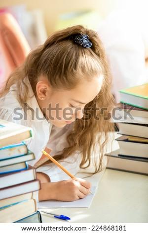 Portrait of brunette schoolgirl surrounded by books doing homework - stock photo