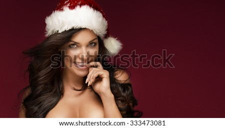 Portrait of brunette sexy woman with red Santa Claus hat. Christmas content.