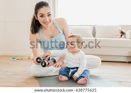 Portrait of brunette woman and baby child sitting on yoga mat with dumbbells and playing together
