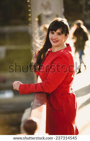 Portrait of brunette woman posing on bridge at cold windy day - stock photo