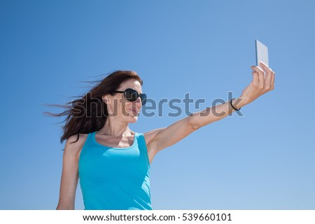 portrait of brunette woman with black sunglasses and cyan shirt smiling and making selfie with mobile phone smartphone with blue sky behind