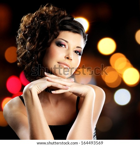 Portrait of brunette woman with fashion hairstyle over night lights  background