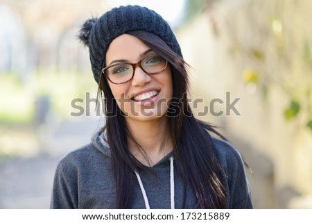 Portrait of brunette young woman with green eyes, wearing green casual clothes, eye glasses and hat, in urban background - stock photo