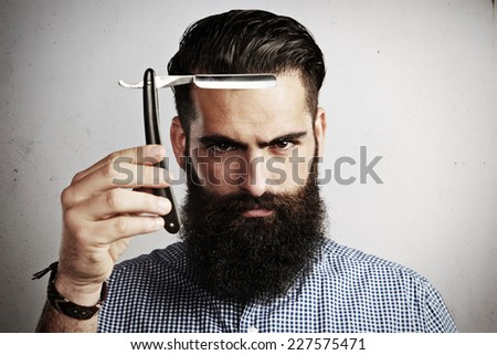 Portrait of brutal man with straight razor - stock photo