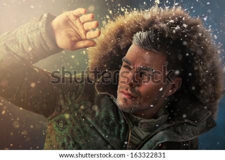 Portrait of brutal sexy man outdoors in winter under snowstorm - stock photo