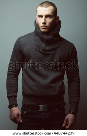 Portrait of brutal young man with short hair and bristle on face wearing sweatshirt, blue jeans and posing over gray background. Bully style. Studio shot