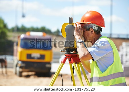 Portrait of builder worker with theodolite transit equipment at construction site outdoors during surveyor work - stock photo