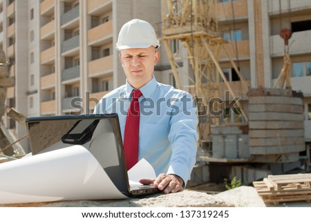 Portrait of builder works at construction site - stock photo