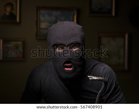 portrait of burglar with crowbar inside a house