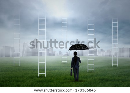 Portrait of business agent holding an umbrella looking at the city - stock photo