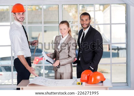 Portrait of business architects. Three architects met in the office to discuss business projects. Successful young people in the construction helmets are on the table - stock photo