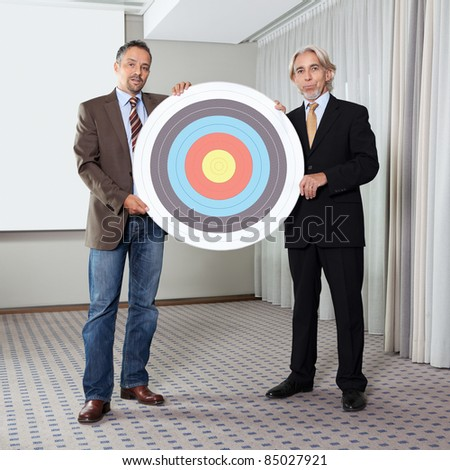 Portrait of business colleagues holding target - stock photo