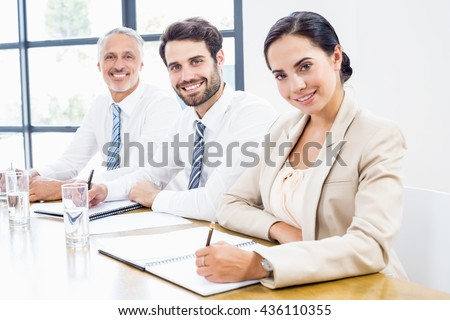 Portrait of business colleagues writing in diary during a meeting - stock photo