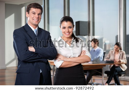 Portrait of business executives with arms crossed with colleagues working in background - stock photo