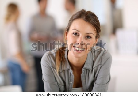 Portrait of business girl sitting on table in office - stock photo