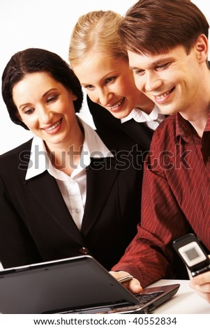 Portrait of business group looking at laptop screen with smiles while man pressing the keys - stock photo