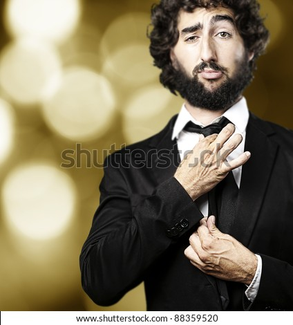 portrait of business man adjusting the tie against a golden lights background