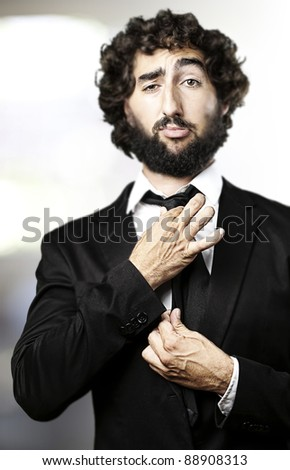 portrait of business man adjusting the tie indoor - stock photo