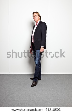 Portrait of business man against white wall in office - stock photo