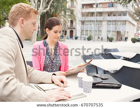 Portrait of business man and business woman sitting together in coffee shop working, reading financial newspaper in city, outdoors. Professional working colleagues in exterior. Busy people lifestyle.